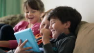 MS Young children sitting on sofa watching tablet device together, smiling