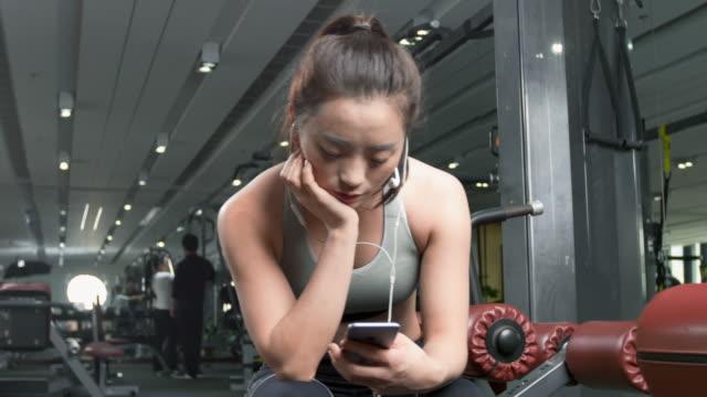 jonge Chinezen met mobiele telefoon in moderne sportschool