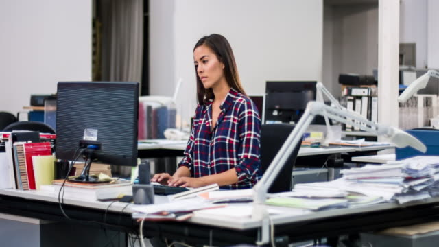 Jonge Colombiaanse vrouwelijke industrieel ontwerper die werkt op kantoor