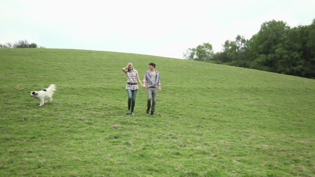 Young couple and dog walking in countryside