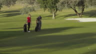 MS young couple approaching green, dropping their bags and enter green; woman putts and holes in two attempts, RED R3D 4K