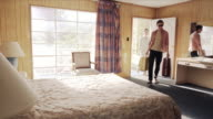 Young couple arrive at Vegas motel, guys drops luggage and jumps onto bed