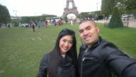 CNEUTRV1093 Young couple at Eiffel tower taking a selfie photo