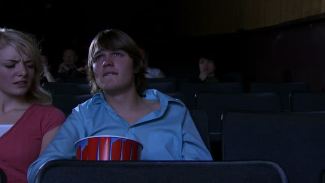 Young couple at movie theater with boy crying