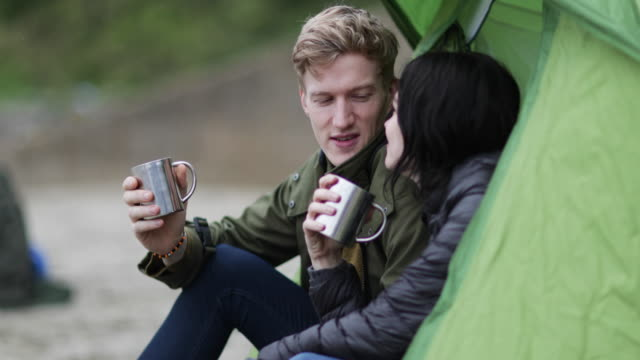 Young couple camping on the beach in fall