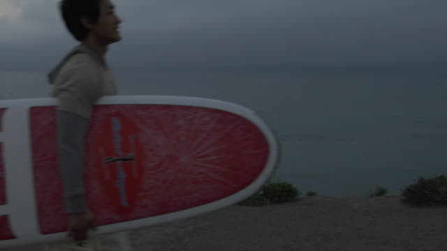 MS, Young couple carrying surfboard on beach at dusk, Los Angeles, California, USA