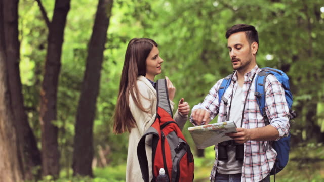 Young couple communicating while hiking in nature and orienteering with help of a map.