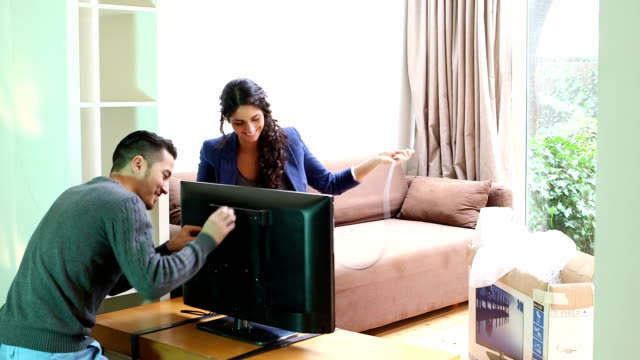 Young couple connecting cable to new television