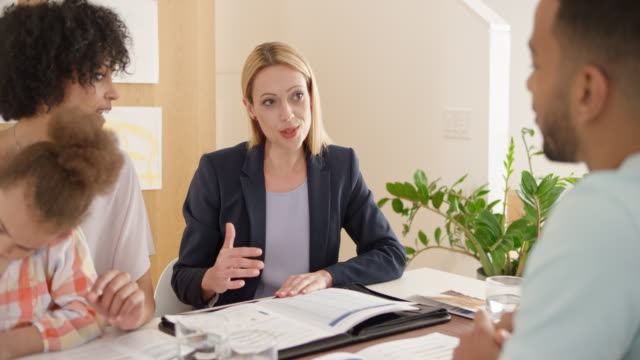 Young couple consulting with female insurance agent at their home
