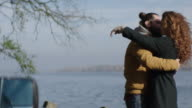 Young couple cuddling by the lake