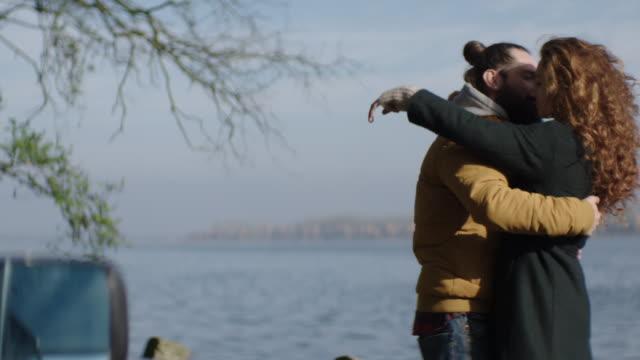 Jong koppel knuffelt aan het meer