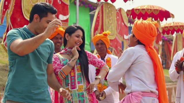 Young couple dancing with folk dance performer, Suraj Kund Fair, Faridabad, Haryana, India