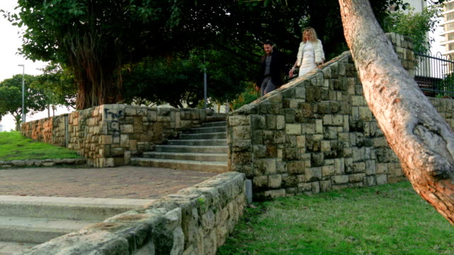 Young couple descends stone park staircase holding hands