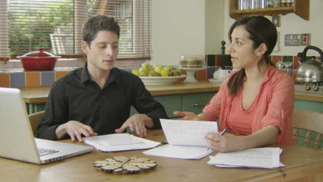 Young couple discussing finance in a country kitchen, both looking at tablet and talking.