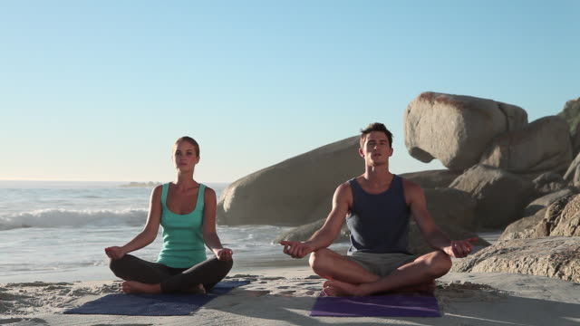 Young couple doing yoga on beach