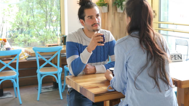 Young Couple Drinking Coffee While Talking At Cafe