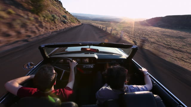 WS Young couple driving convertible at sunset on desert road/Washington, USA