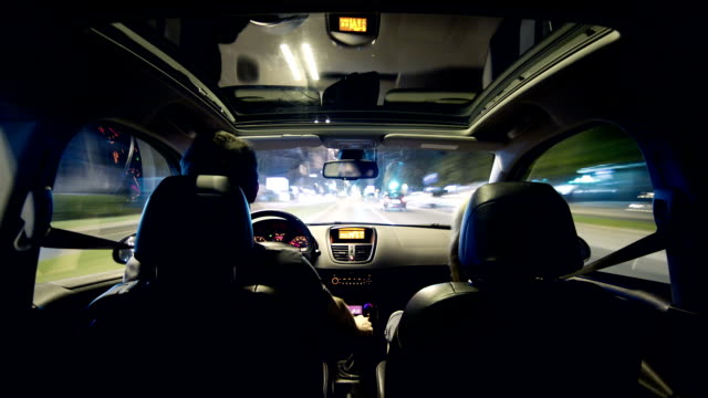 Young couple driving in a car through city at night