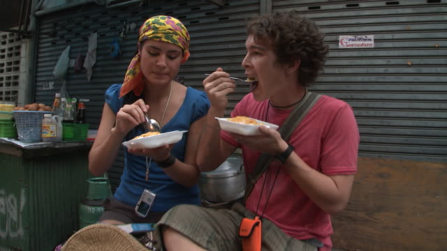 WS ZI CU Young couple eating food in city backstreet, Bangkok, Thailand