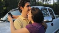 CU Young couple embracing and flirting while woman texting on PDA / Madison, Florida, USA