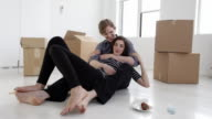 MS Young couple embracing and rough housing sitting on floor in empty apartment