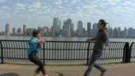 WS ZI PAN Young couple embracing on pier with New York City skyline in background / Jersey City, New Jersey, USA