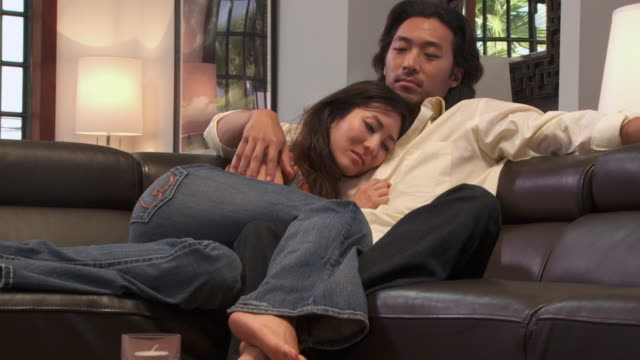 ZI, CU, Young couple embracing on sofa, Los Angeles, California, USA