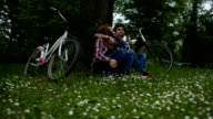 HD: Young couple enjoy break after riding bicycle outdoors.