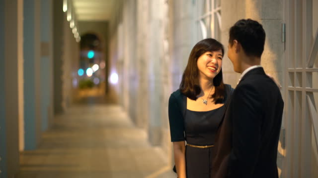 WS Young couple happily talking together at night.