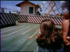 A young couple has fun at an amusement park circa 1969 The couple runs toward a Ferris Wheel rides a slide rides on a merry go round rides a small...