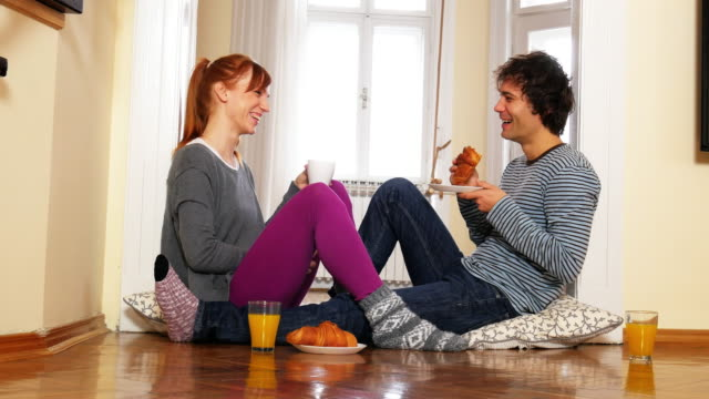 Young couple having snack at home, enjoying their love and marriage