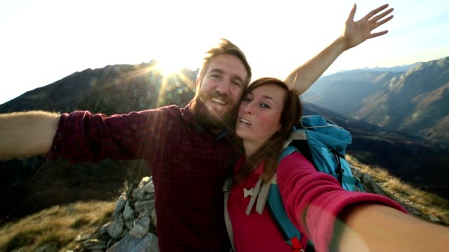 Young couple hikers taking selfie on mountain top
