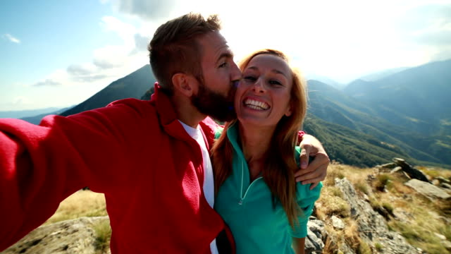 Young couple hiking, taking a selfie on mountain peak