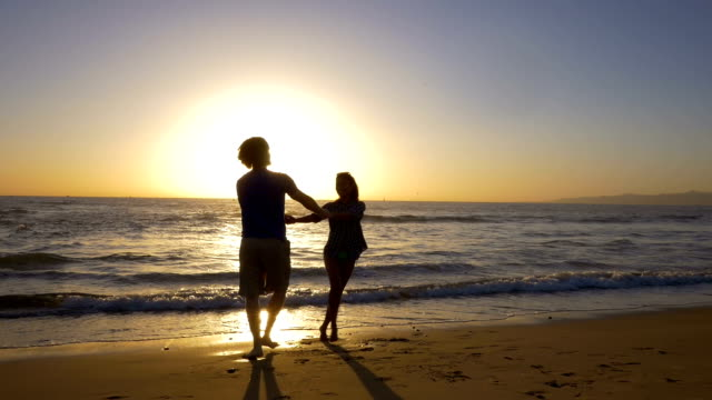 Young couple holding hands and spinning on beautiful ocean beach at sunset.