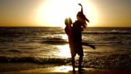 Giovane coppia tenendo le mani e filatura sul bellissimo oceano sulla spiaggia al tramonto.