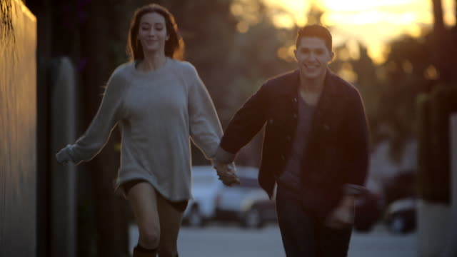 Young couple holding hands running towards camera