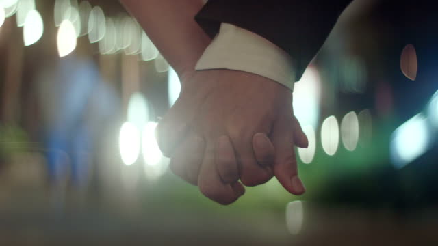 Young couple holding hands together ,close up
