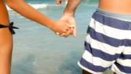 Young couple holding hands while entering the sea water