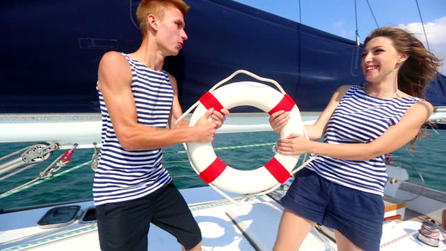 Young couple in a playful fight for lifeline yacht