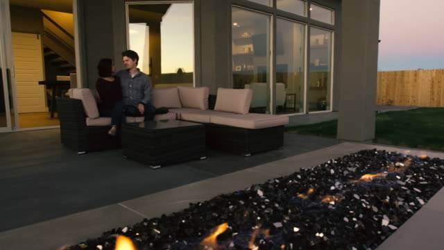 Young Couple in Back Yard at Outdoor Fireplace