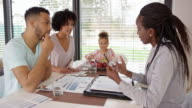 Young couple in consultation with insurance agent at their home