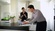 MS Young couple in kitchen using laptop and smartphone