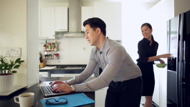 MS Young couple in kitchen using laptop computer