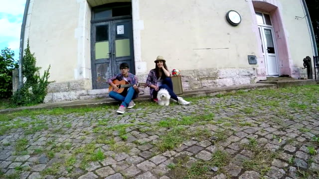 Young couple in love playing acoustic guitar in the park