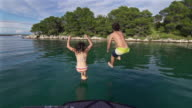 Young couple jumps into the sea from a boat