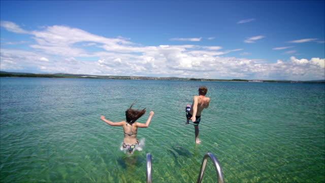 Paar Sprünge ins Meer vom Pier Super-Zeitlupe