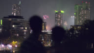 Young couple kiss and stare out as fireworks burst over city skyline