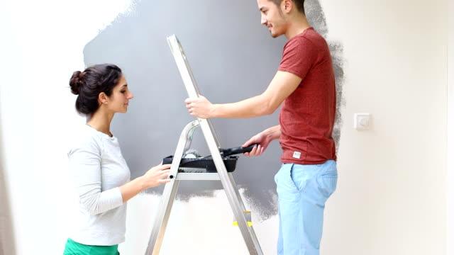 Giovane coppia baciare e parete con rullo pittura