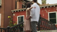 SLO MO MS Young couple kissing footbridge / Venice,Italy