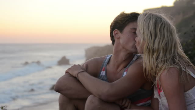MS R/F Young couple kissing on cliff watching beach sunset / Malibu, California, United States